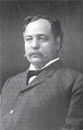 A portly man with black, wavy, receding hair wearing a black jacket and tie and white shirt