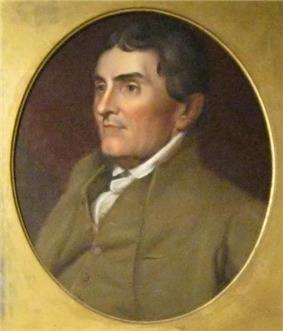 Portrait shows a clean-shaven man with dark brown hair wearing a brown coat over a white shirt.