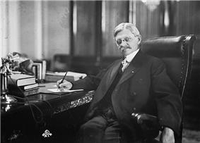 A man sitting at a desk looking directly at the photographer; one hand is holding a pen to a document on his desk while the other is hanging over the arm of his high backed chair, his legged stretched forwards, he is wearing a suit, neck tie, and glasses, and has a serious expression.