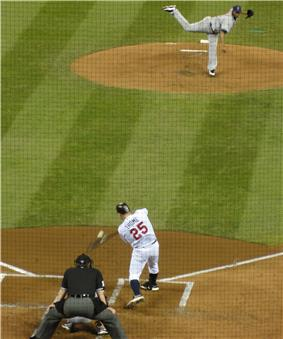 The moment of contact between Thome's bat and a pitch from Fausto Carmona; the image is distorted through the black screen protecting those sitting behind home plate.