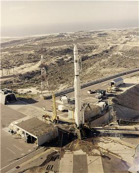 Photograph of the Thor-Agena vehicle on the launch pad at Space Launch Complex 10, surrounded by scrub vegetation and various support buildings, the Pacific Ocean in the distant background.