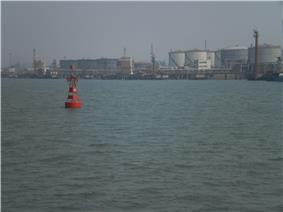 A red port-side buoy with an oil wharf and tankers in the background