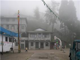 A two-storeyed building to the right of a four-storeyed building. A basketball court in the foreground and a couple of vehicles parked on either side. Foggy atmosphere, with trees in the background.