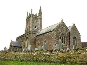 Stone church view from a low angle. The church has a simple tower and there are gravestones in the churchyard surrounding it