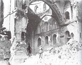 Black & white image of a lone soldier gazing at synagogue interior through a destroyed side wall