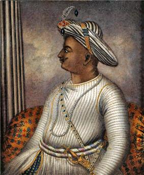 Side portrait of man in turban wearing knitted tunic with gold sword