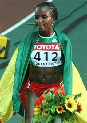 Tirunesh Dibaba in a green running vest covered in a flag, holding a bouquet of flowers