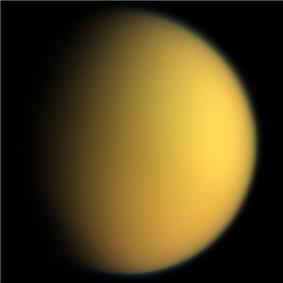 An orange spherical body is half illuminated from the right. The terminator is running from the top to bottom slightly to the left off the center. Both limb and terminator are fuzzy due to light scattering in the atmosphere.