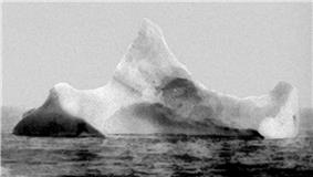 Black and white photograph of a large iceberg with three