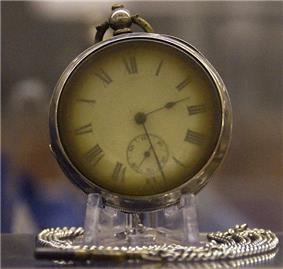 Photograph of a brass pocket watch on a stand, with a silver chain curled around the base. The watch's hands read 2:28.