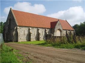 Long stone building with buttressed walls and red tiled roof.