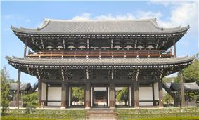 A large two-storied wooden gate with white walls, a veranda on the upper story and a hip-and-gable style roof. Two small wooden open structures with gabled roofs are placed next to it on either side.
