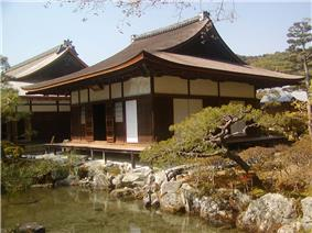 A single-storied wooden building with a hip-and-gable roof, white walls and wooden sliding doors.