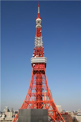 The orange and white lattice frame of Tokyo Tower rises up in front of a clear, blue sky.