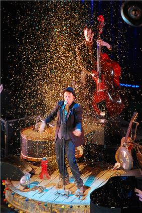 A man performing on-stage, surrounded by confetti. Several instruments surround him and behind him a man is playing a double bass.