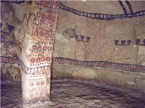 Interior of a cave with wall paintings of geometrical figures in red, black and white.
