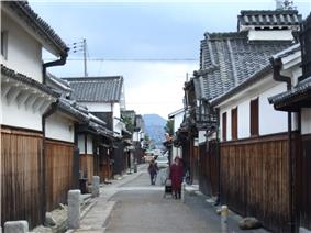 A narrow street lined by houses with a wooden lower part, a white upper storey and tile roofs.