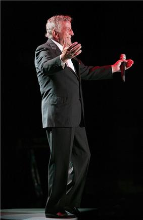 An older man holding a microphone in one hand, his arms held out, smiling and wearing a black suit with a white dress shirt.