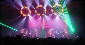 Musicians performing on stage in front of a crowd under many lights of different colors.
