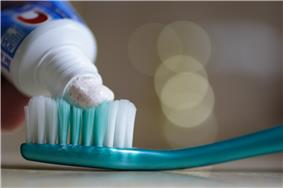A tube applying toothpaste to a toothbrush.