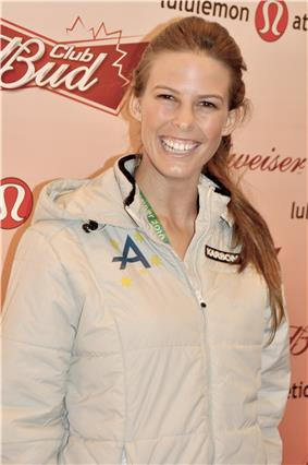 Photo of the torso and head of a female with a long brown ponytail who is smiling broadly. She is wearing a white nylon tracksuit with a green A on the right chest area. Behind her is an advertising background for Budweiser.
