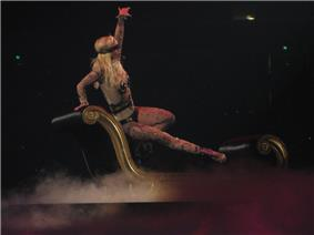 Image of a blond woman. Her right hip is resting on a black divan, with her right leg extended to the end of the divan. Her left hand is extended in the air, while her right hand is grabbing the top of the divan. She is wearing a flesh-colored body suit with tattoos and nipple tassles. She is sporting a black blindfold and singing into a wireless microphone. The divan is surrounded by smoke.