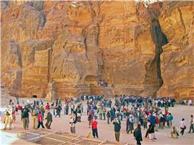 A large variety of people taking photographs of something just beyond the camera, in a canyon with a rocky rear wall