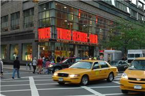 A street view of a store front prominently features a yellow taxi in front of the store. The walls contain clear windows with the phrase