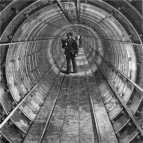 Etching of a circular tunnel made of bolted segments. A walkway of boards runs down the centre of the tunnel and a man in workman's clothes with a bag over his shoulders stands in the middle distance