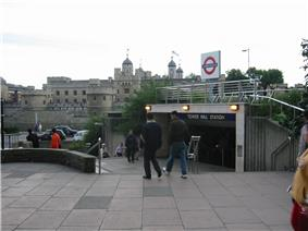 A grey, many-windowed castle with flags flying from its turrets in the background, several people walking in the foreground, and a bright sky above