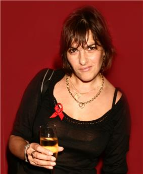 Tracey Emin, holding a wine glass filled with a translucent, peach-colored liquid. She is wearing a black top, with a red ribbon attached.