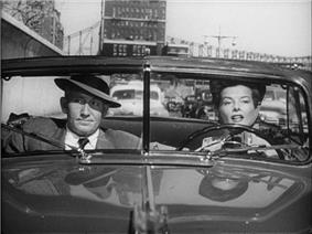 Screenshot of Hepburn and Spencer Tracy sat in an open-top car in mid-conversation. He looks unimpressed.