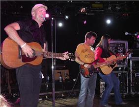 Three man on stage playing three different guitars.