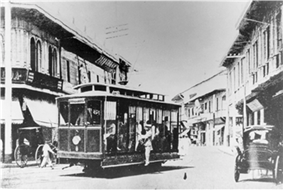 An electric trolley with a man hanging off one side rounds a corner of a street lined by two-story stores and horse-drawn kalesas.