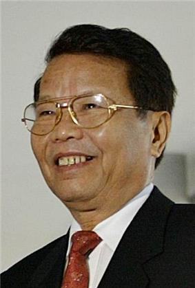a smiling man with black hair, wearing glasses, and dressed in a suit with a red tie