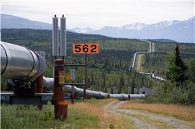 Oil pipeline winding through cold Alaskan country-side. In the background are mountains, partly snow-capped
