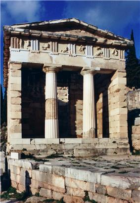 A partially ruined marble building with a porch with 2 columns supporting a pediment and an open doorway beyond