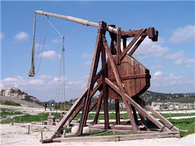 A tall wooden structure with a throwing arm counterbalanced by a large weight
