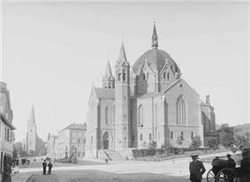 Large, fanciful building with towers, pointed arches, and a large dome in the center, topped by a spire.