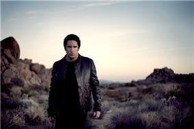 A man dressed in black walking through a desert at sunset.