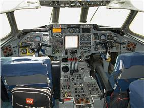 The flight deck of a jet airliner with many instruments and controls. Two pilots' seats have small bags hanging on them, one showing the words