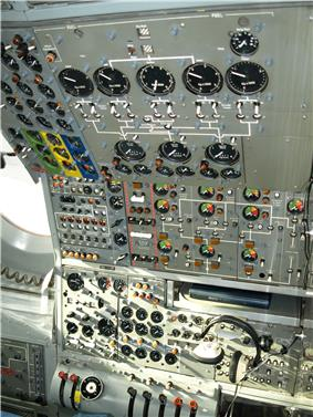 An airliner flight deck control panel with many instruments and switches. A pair of headphones hang from the panel.