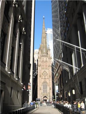 Ground-level view of a large, brown church with Gothic architecture and a tall, tapering spire that is only partially visible in the image