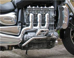 Closeup picture of a motorcycle engine with three heavily chromed exhaust pipes coming out of the side