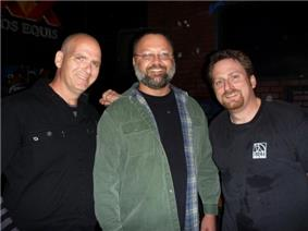 three middle-aged men stand together facing the camera and smiling