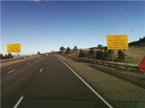 A highway near the top of a ridge. On either side of the highway are big yellow signs reading,