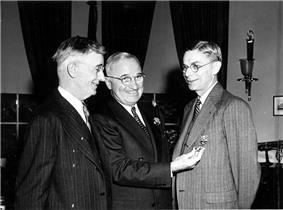 Three smiling men in suits