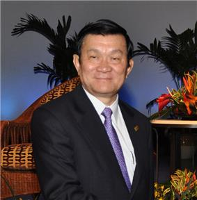 a smiling man with black hair, dressed in a dark suit with a white shirt and purple tie