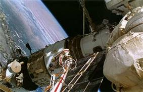 A man dressed in a white spacesuit with a red stripe seen clinging to the end of a boom-like crane, moving over a white space station module. Various trusses, solar arrays and other structures project from the module, and the Earth is visible in the background.