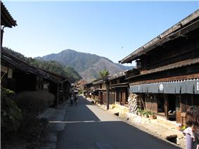 Small street lined by wooden two-storeyed houses.